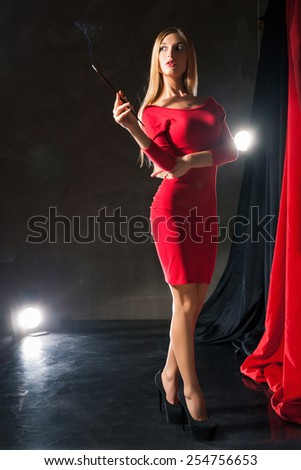 Glamorous young woman  with cigarette wearing red dress standing on stage.  - stock photo