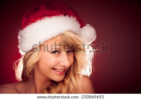 Glamorous young woman with Santa claus hat sending best  wishes for christmas - stock photo