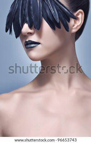 Glamour and beauty shot of a beautiful model with creative make-up of black bird feathers concealing her eyes like a mask. High-end retouching. - stock photo