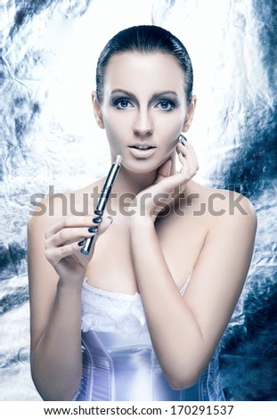 Glamour and bizarre portrait of young and beautiful woman with the electronic cigarette in creative winter style - stock photo