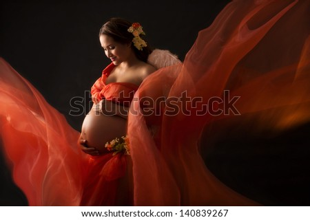 Glamour and style of young pregnant woman with orange material on the black background - stock photo