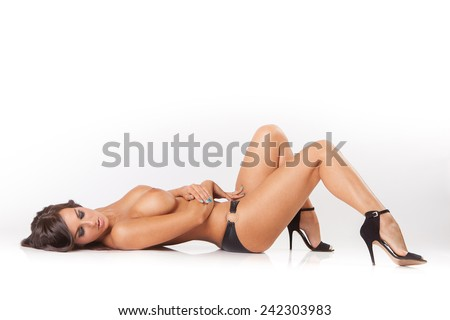 glamour attractive brunette girl with big breasts lying on white floor - stock photo