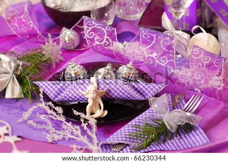 glamour christmas table decoration in purple color with angel on glass plate - stock photo