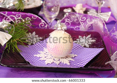 glamour christmas table decoration in purple color with shining ball and snowflakes on glass plate - stock photo