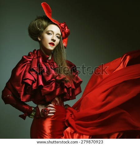 Glamour fashion model in elegance red costume with red hat. Studio shot. - stock photo