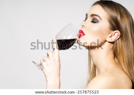Glamour girl drinking red wine on white background - stock photo
