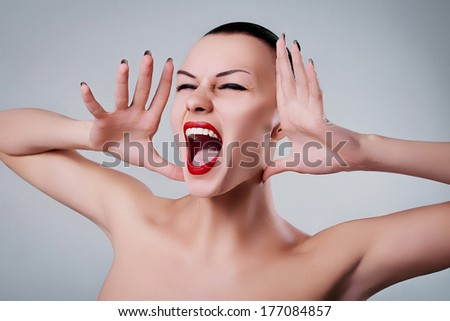 glamour portrait of a beautiful screaming young woman red lips - stock photo