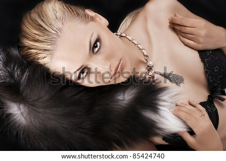 glamour portrait of a sexy blonde laying on black just wearing fur and a necklace - stock photo