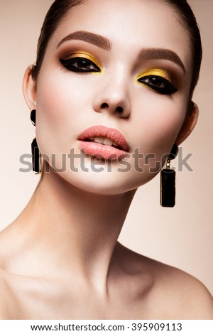 Glamour portrait of beautiful girl model with makeup. Fashion shiny highlighter on skin, sexy gloss lips make-up and dark eyebrows. - stock photo