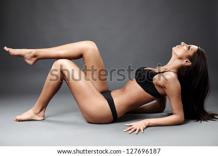 Glamour profile of perfect exotic dancer in sexy lingerie lying on the ground. - stock photo