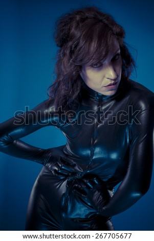 Glamour, sexy brunette in black latex bodysuit tight and wild poses - stock photo
