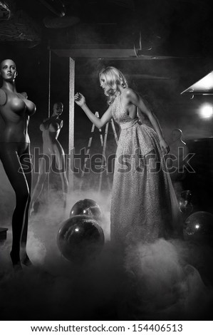 Glamour style photo of posing girl with mannequins - stock photo