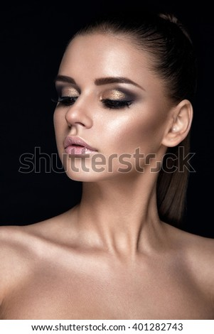 Glamour woman portrait. Young lady is posing on black background. High fashion. Beautiful makeup. Nude and gold colors.  - stock photo