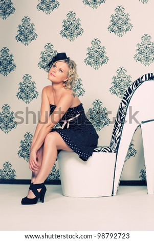 Glamoured retro styled portrait with blond model sits on high heel shoe - stock photo