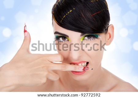 Glamourous closeup  portrait of a sexy aggressive woman biting her middle finger. Fashion eyeliner makeup on model eyes. Cosmetics and make-up. Sexy wild vamp style - stock photo