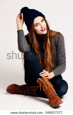 Glamourous portrait of the young beautiful woman in leather boots and autumn clothes posing over white background, sitting on the floor. Studio shot. Hipster style.  - stock photo
