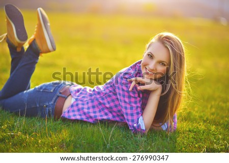 Glamourous portrait of the young beautiful woman in stylish jeans and colorful shoes outdoor. Beautiful Young Woman Outdoors. Enjoy Nature - stock photo