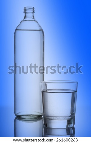 glass and bottle full of natural water, on blue background - stock photo