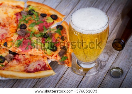 Glass and bottle of beer, pizza on wooden background - stock photo