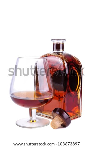 glass and bottle of cognac or brandy with cork isolated on a white background - stock photo