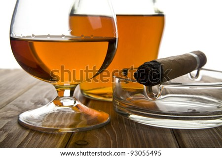 glass and bottle of cognac with a cigar on a white background - stock photo