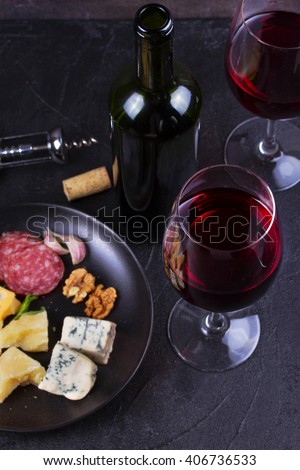 Glass and bottle of red wine, cheese, bread, garlic, nuts, salami on gray stone texture background. View from above - stock photo