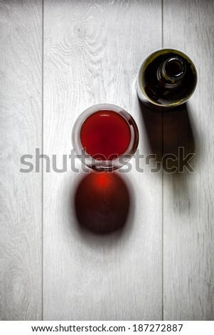 Glass and bottle of red wine with cork on white wooden table. Top view - stock photo