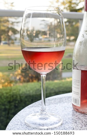 Glass and bottle of rose wine outdoor - stock photo
