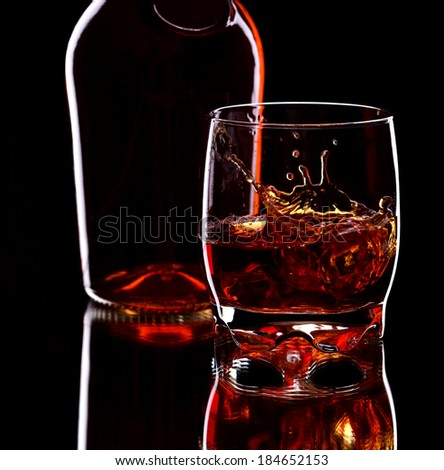 Glass and bottle of whiskey with splash on dark background, selective focus on the glass - stock photo