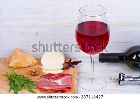 Glass and bottle of wine, cheese and prosciutto - stock photo