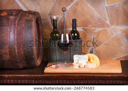 Glass and bottle of wine, cheese and prosciutto, old wooden barrel - stock photo