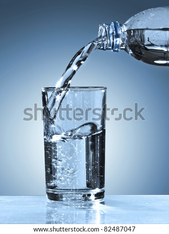 Glass and bottle with pure water on blue background - stock photo