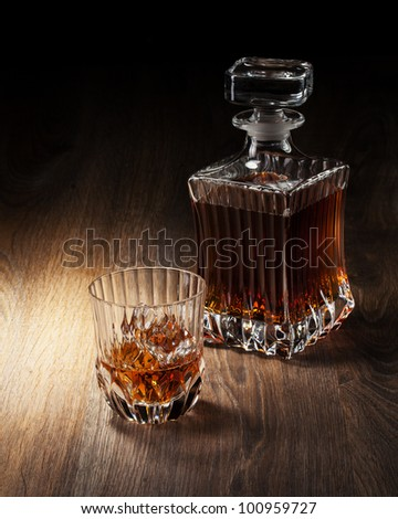 glass and bottle with whiskey on a wooden table - stock photo