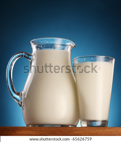 Glass and jar of milk on a blue background. - stock photo