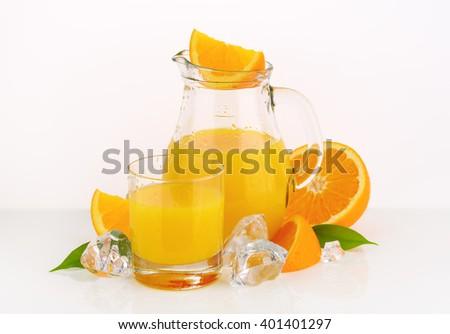 glass and jug of fresh orange juice on white background - stock photo