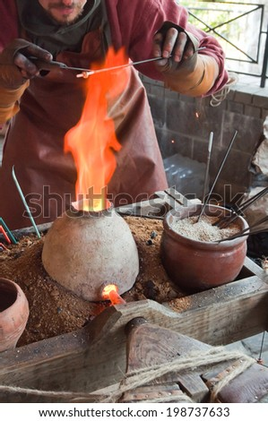 Glass artist in his workshop: making glass beads in traditional style. - stock photo