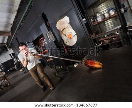 Glass artist with safety glasses and blowpipe forming a vase - stock photo
