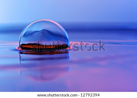 Glass ball floating in colored water - stock photo