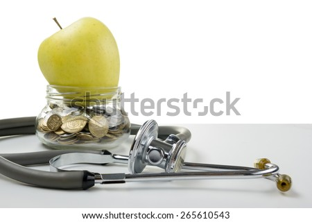 Glass bank with coins, green apple and medical stethoscope. Medical costs, financial concept - stock photo