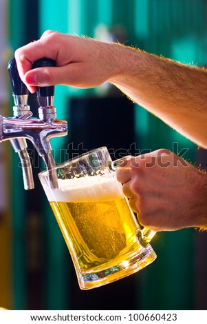 glass being filled with draft beer by barman - stock photo