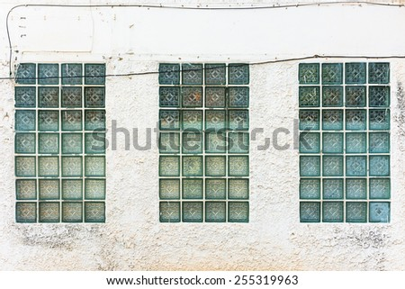 Glass block on the old concrete wall - stock photo