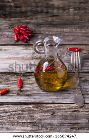 Glass bottle of olive oil with red hot chili peppers and vintage fork over old wooden background. See series - stock photo