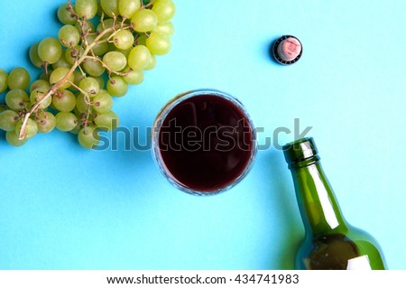 Glass, bottle of wine, green grapes on a blue background - stock photo