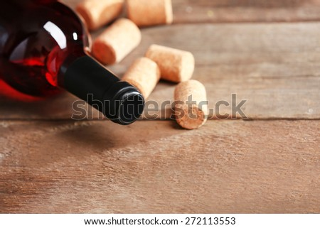 Glass bottle of wine with corks and corkscrew on wooden table background - stock photo