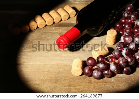 Glass bottle of wine with corks and grapes in dark with light on wooden table background - stock photo