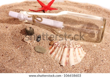 Glass bottle with note on sand shore with seashells - stock photo