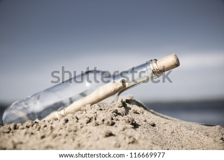glass bottle with note washed up on the beach - stock photo