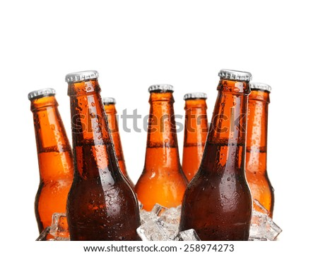 Glass bottles of beer in ice cubes isolated on white - stock photo