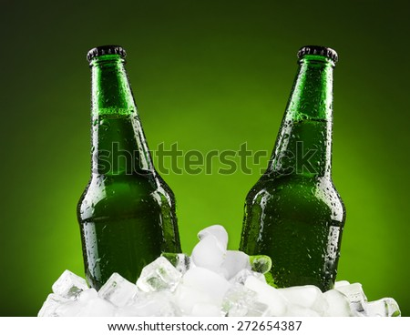 Glass bottles of beer in ice cubes on color background - stock photo