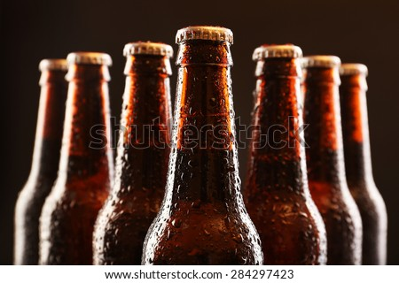 Glass bottles of beer on dark background - stock photo
